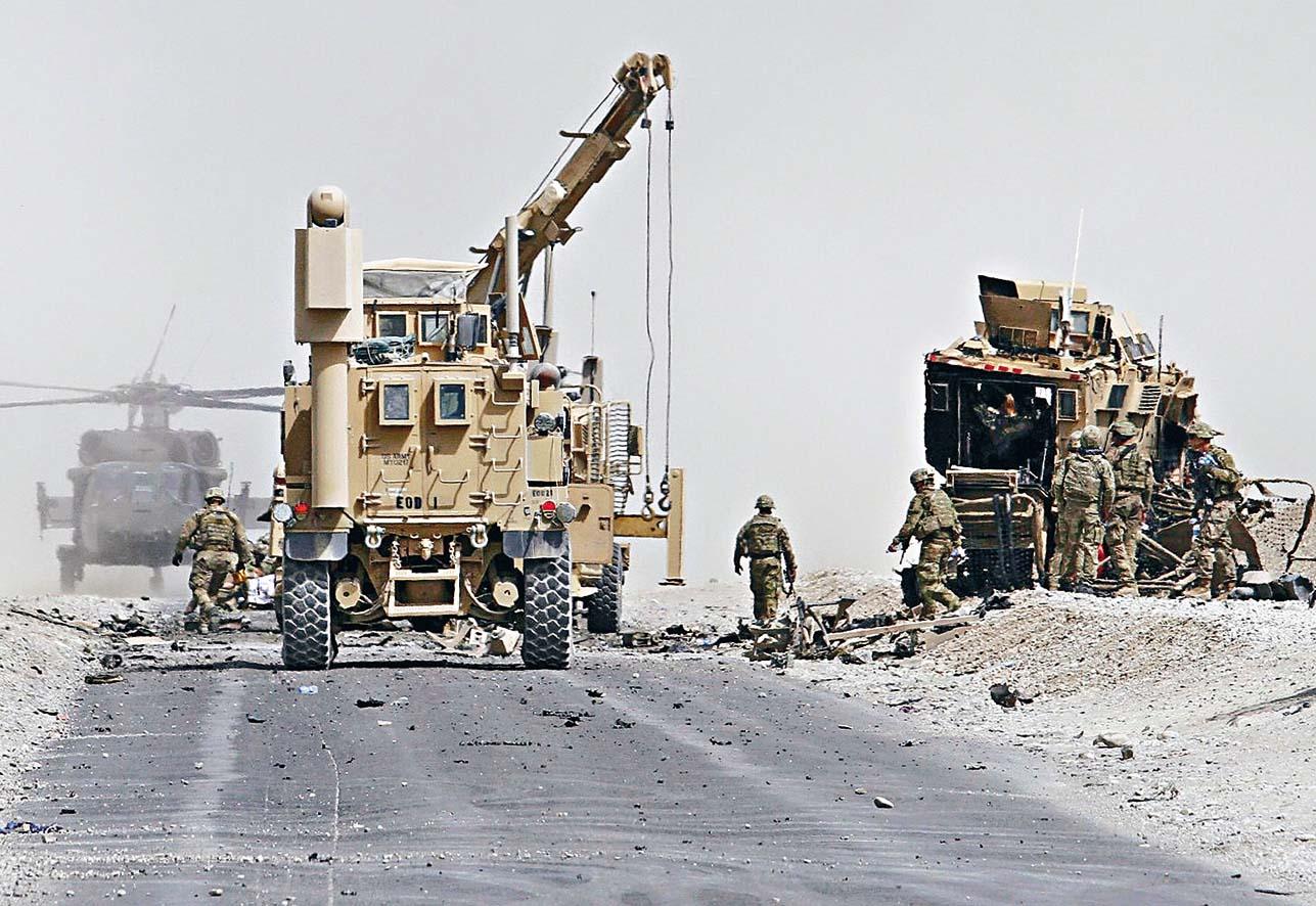 二○一七年八月坎大哈省發生自 殺式襲擊後,美軍在現場評估一輛 北約裝甲車的受損情況。 路透社