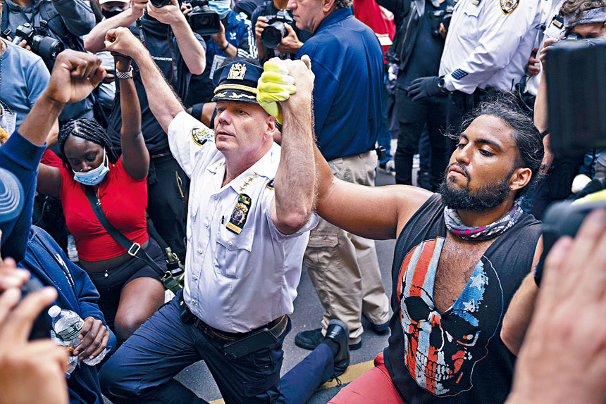莫納漢向抗議者單膝下跪呼籲和平。美聯社
