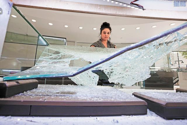 沙加緬度市中心的沙里夫首飾店(Sharif Fine Jewelers)遭破壞,員工看著被打碎的玻璃櫃。美聯社