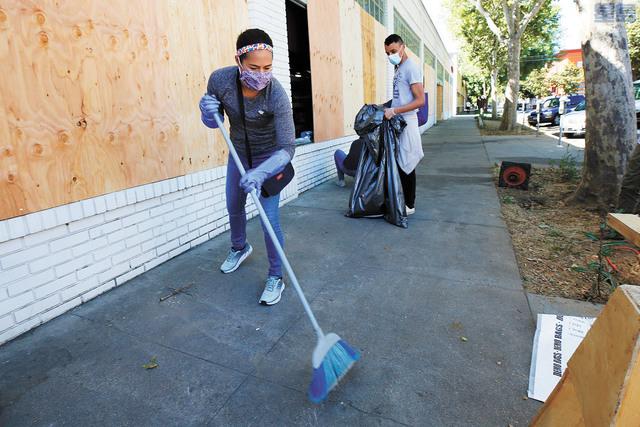 義工星期一在市中心遭破壞的店鋪外清掃。美聯社