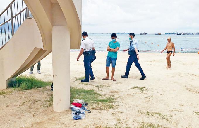 警員在沙灘調查,發現女死者遺下物品。