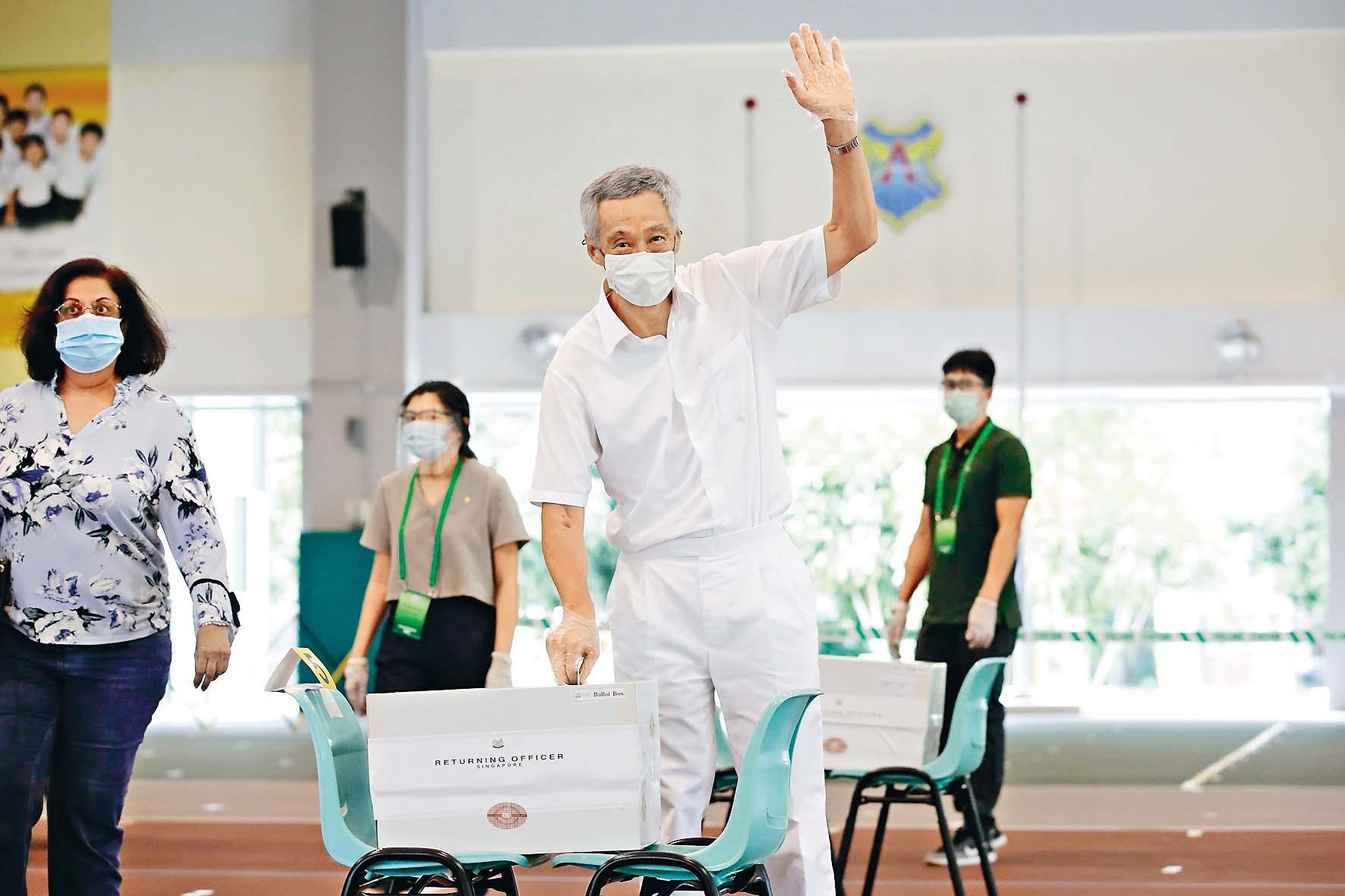 總理李顯龍昨天戴着口罩到票站投票。