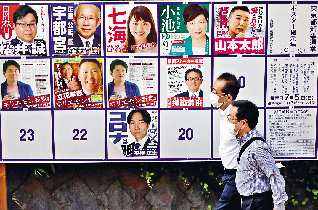 ■東京街頭貼着都知事候選人的海報。 路透社