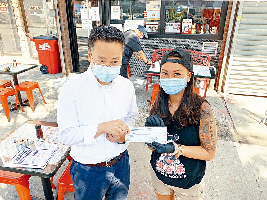 法拉盛商改區執行主任余鈿崧向參加戶外用餐計劃的劉穎諭(右)送贈的100元補貼安裝費用支票。