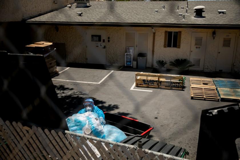 雷奧維斯塔療養中心員工丟棄一大袋用過的防護設備。聖地牙哥聯合論壇報