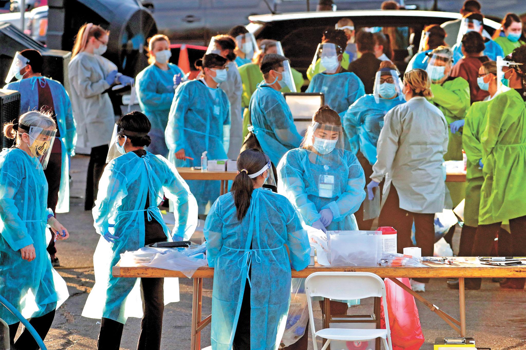 在美國新冠病毒確診病例不斷攀升之際,特朗普政府通知美國國會和聯合國,美國正式退出世界衛生組織。圖為醫護人員為核酸測試做準備工作。美聯社