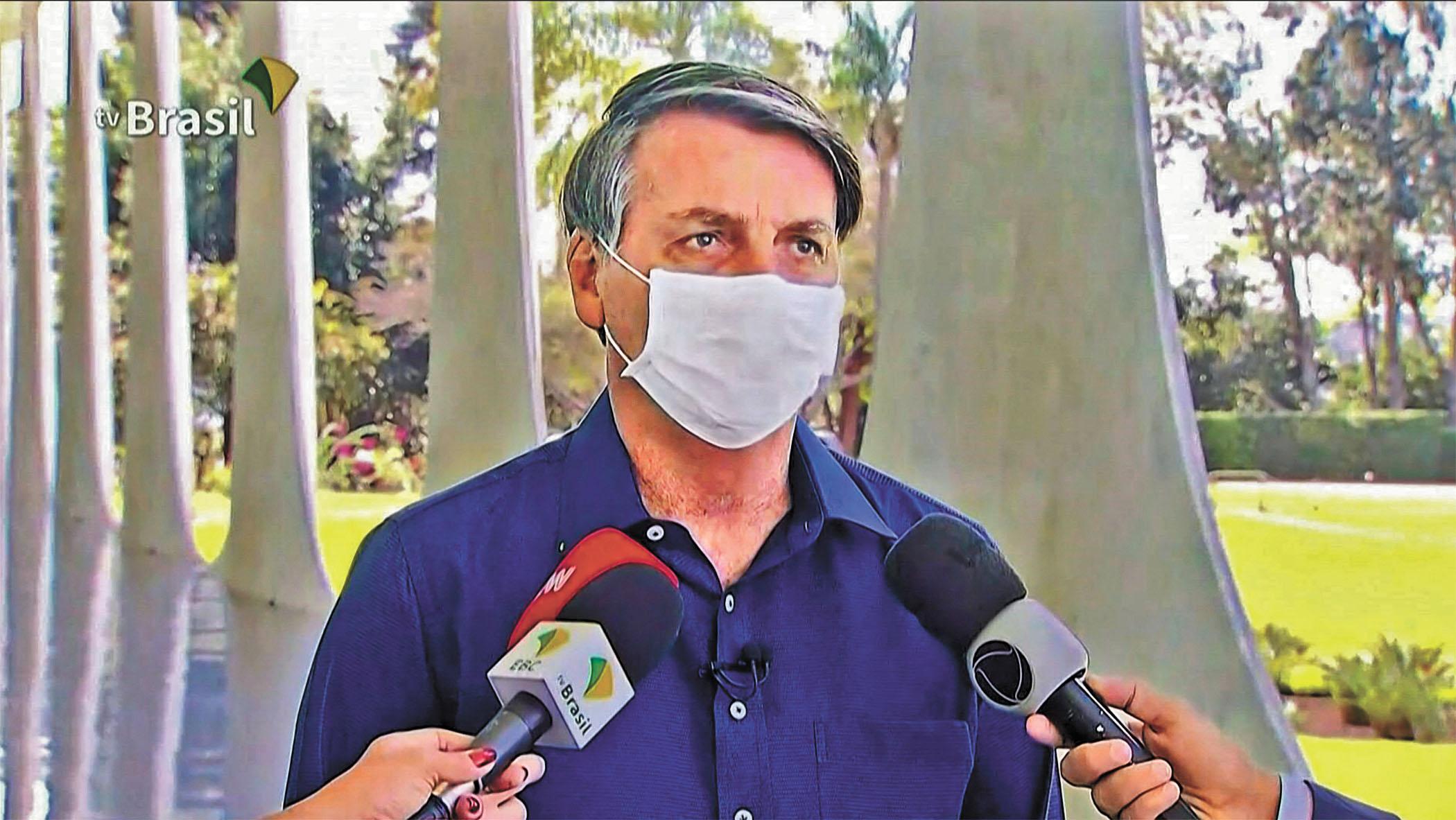 巴西總統在採訪中承認自己感染新冠病毒,正說著話突然後退並摘掉口罩。法新社/網上圖片