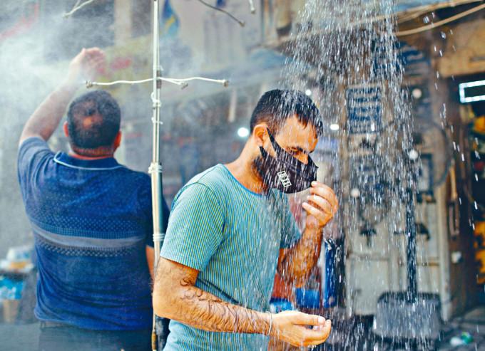 巴格達周二居民在戶外淋花灑降溫。