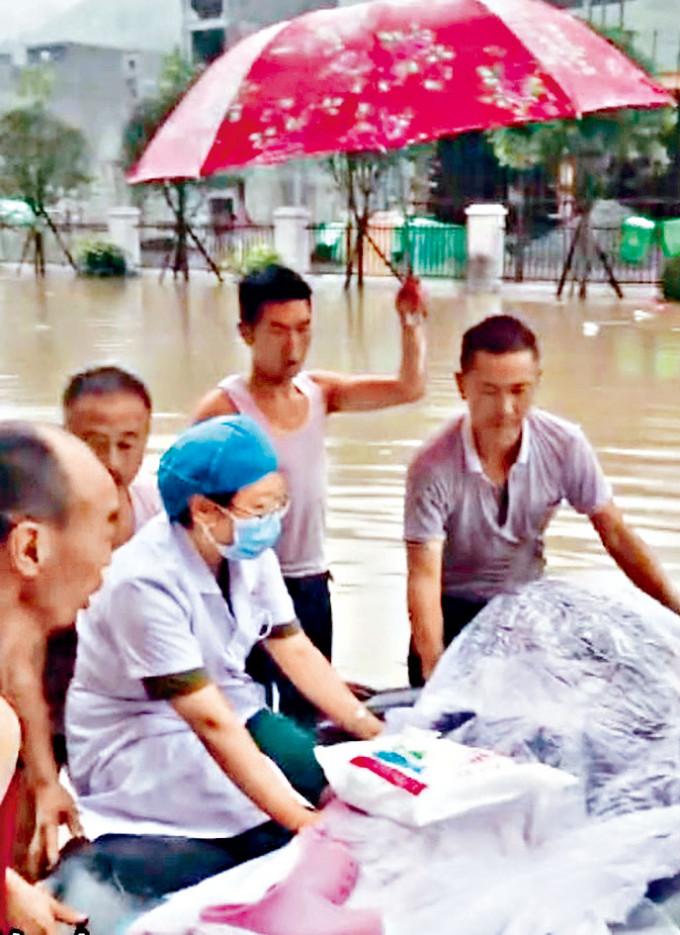 醫生和居民在洪水中守護着臨盆的孕婦。