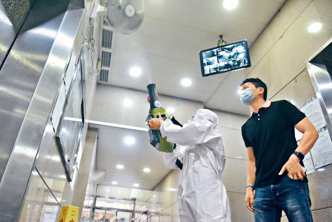 穿着防護裝備人員到爆疫的新發茶餐廳附近民居噴灑消毒劑。