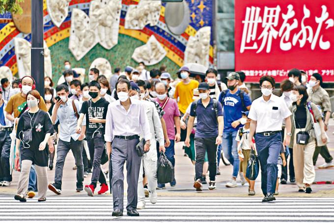 東京市民昨天戴着口罩上街。