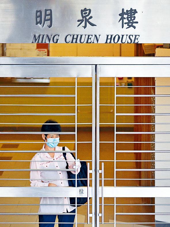 一名明泉樓居民手持紙巾推門,避免感染。