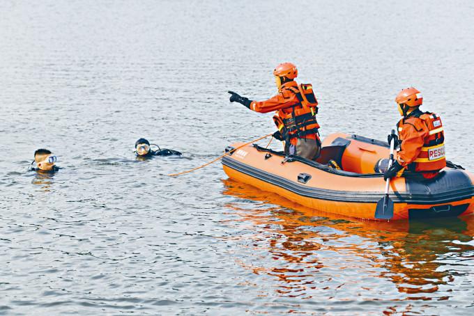 救援人員在巴士墜湖現場搜救。