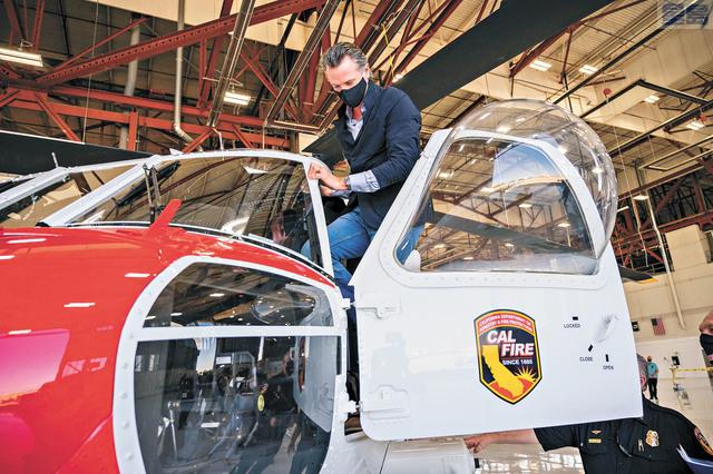 紐森9日到沙加緬度的加州消防局基地,討論州府同時防範疫情與山火的準備,期間登上消防直升機參觀。美聯社