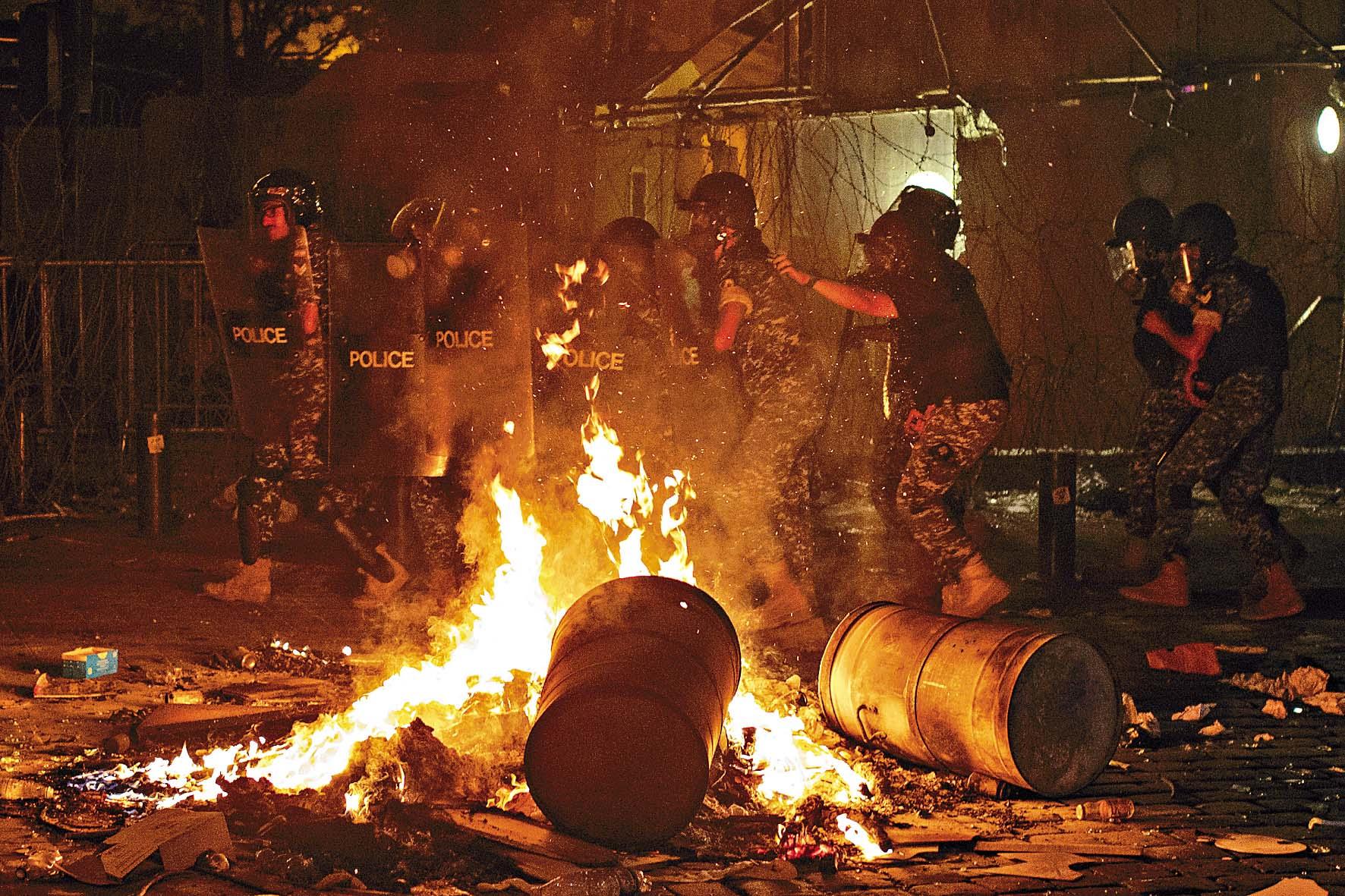 反政府示威者周五在貝魯特街頭縱火,保安部隊上前驅散人群。