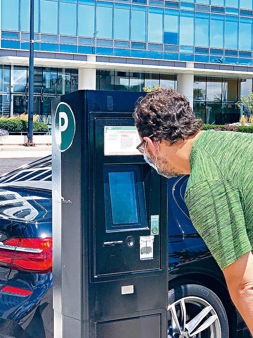 在靠近千禧公園的路邊計時停車器,一名駕駛人正在付停車費。梁敏育攝