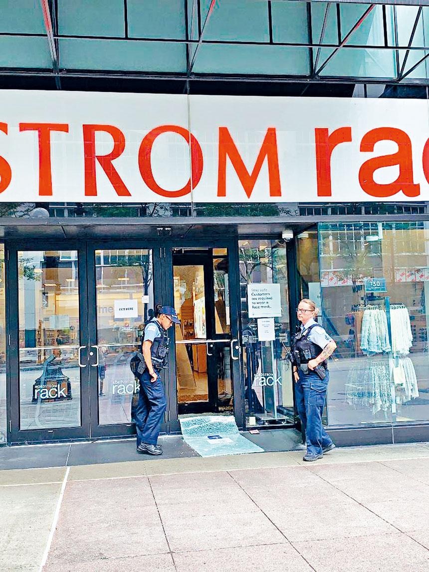 兩名精疲力盡的警員,把守在被砸破的商店門口。梁敏育攝