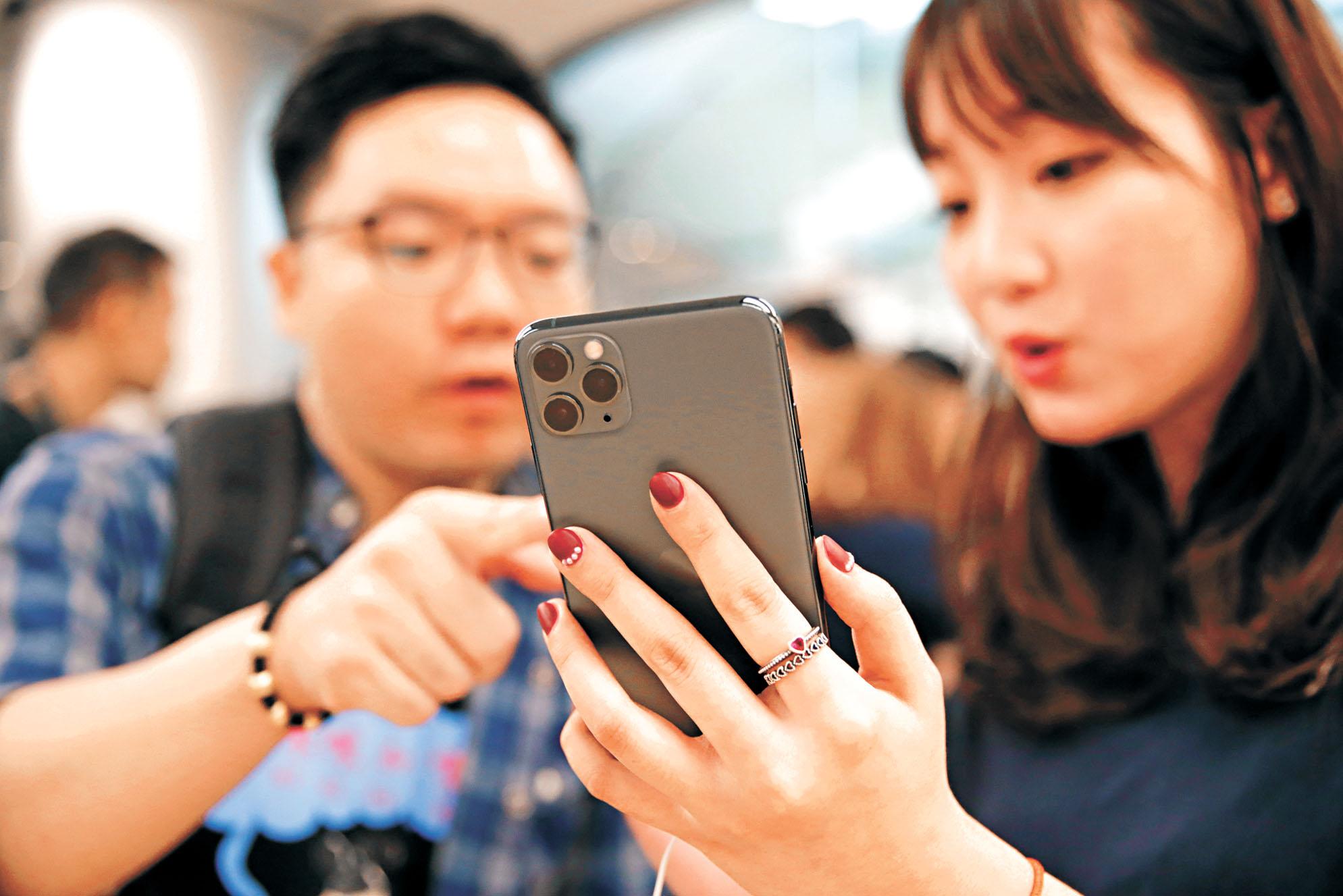 圖為北京市民在試用新款iPhone。路透社資料圖片