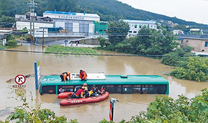 南韓坡州市周四有巴士被洪水淹浸,乘客被救到艇上。