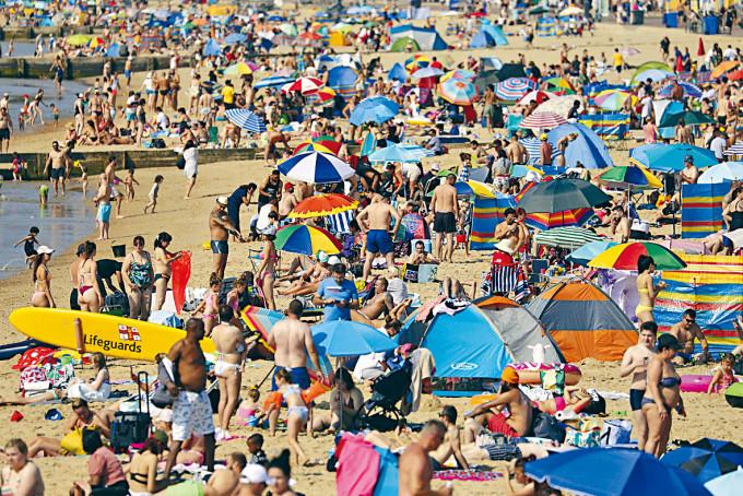 英國伯恩茅斯市的海灘周日擠滿泳客。
