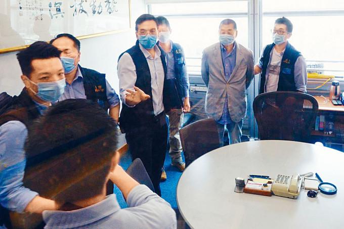 壹傳媒創辦人黎智英(右二)被鎖上手銬,押返其集團總部大樓協助搜查。