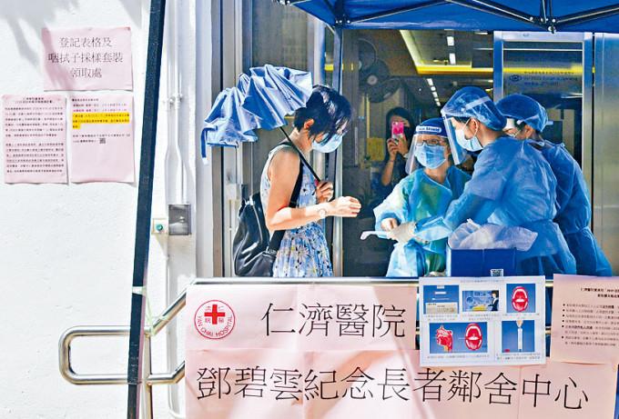 石硤尾邨內仁濟醫院鄧碧雲紀念長者鄰舍中心外,市民領取咽喉拭子採樣套裝。