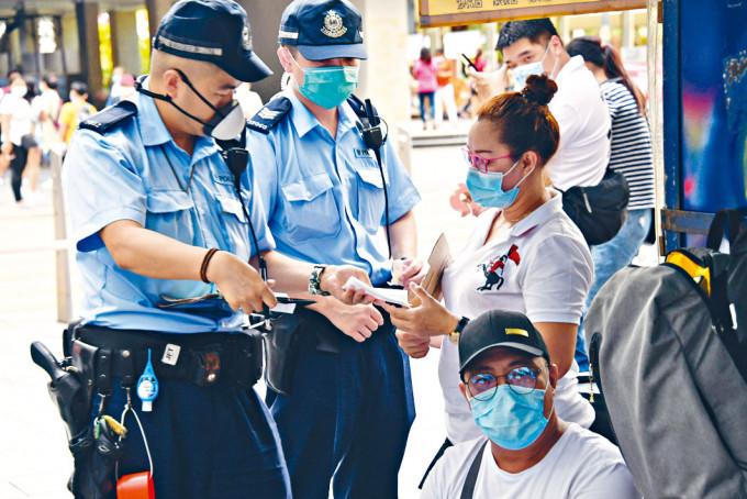 警員向違反「限聚令」的人士發出告票。