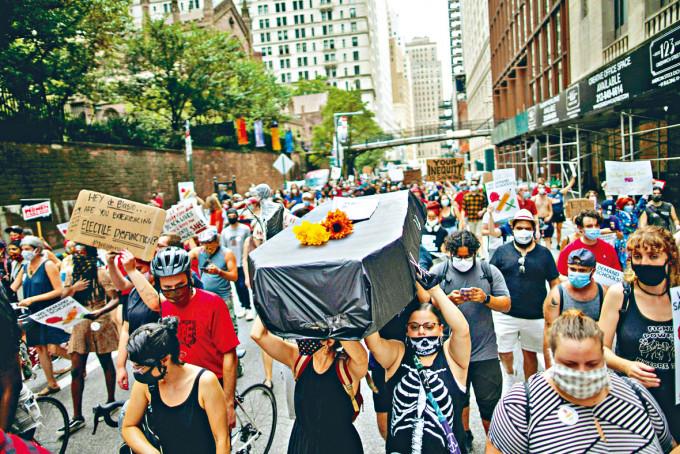 紐約反對學校重開示威者抬着假棺材遊行,象徵染疫死亡學生。