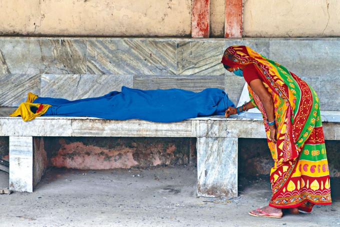印度比哈爾邦醫院新冠死者遺體等候運走,女親屬在旁點香。