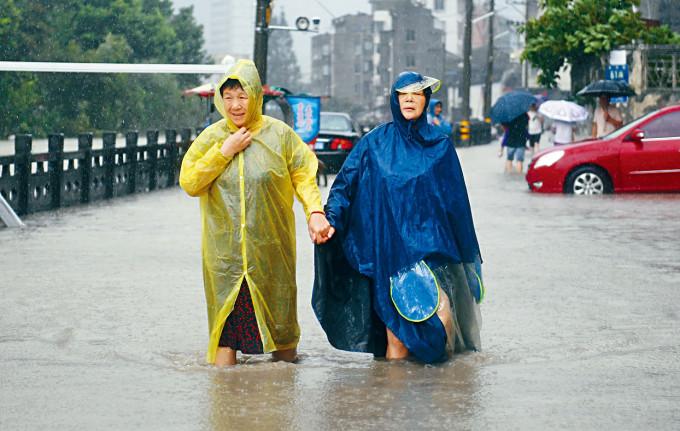 颱風「黑格比」登陸,兩名溫州居民在積水中前行。