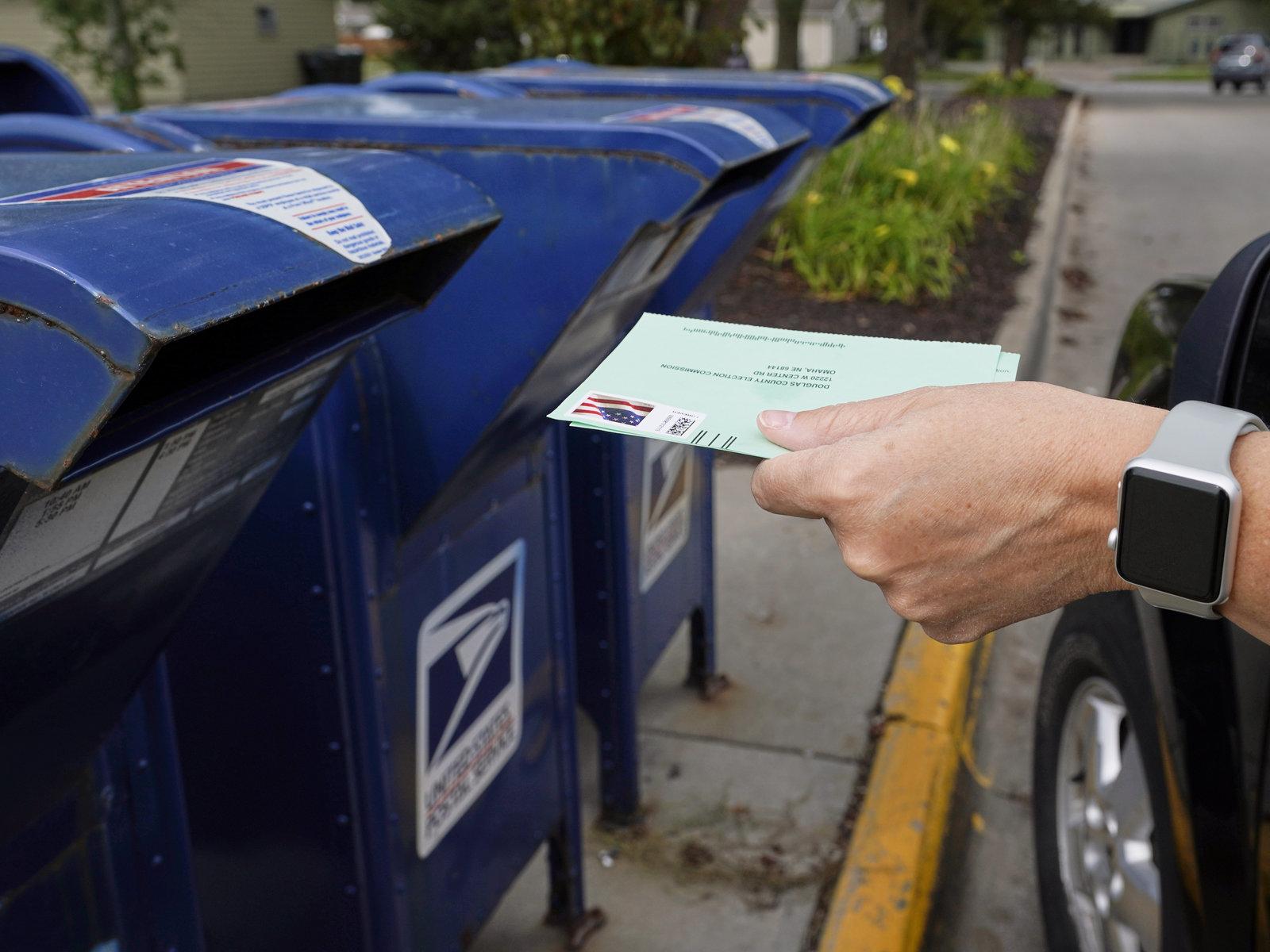 眾議院通過向郵政總局提供250億美元後,以保證11月大選的郵寄投票順利。圖為奧馬哈的選民將郵寄選票的申請投到郵箱中。    美聯社