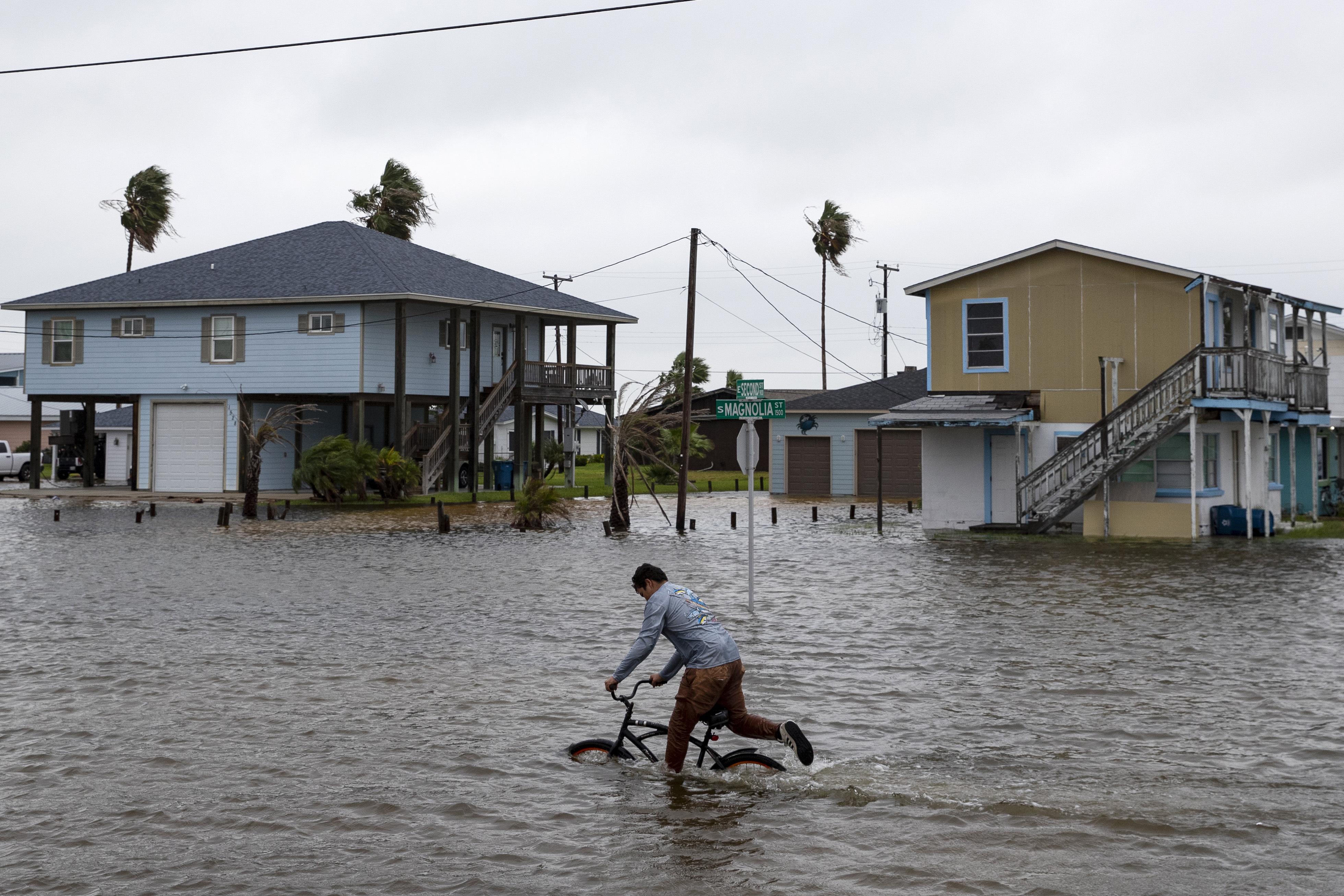 雖然熱帶風暴貝塔臨近,一個男孩21日仍在德州羅克波特淹水的街上騎自行車。    美聯社