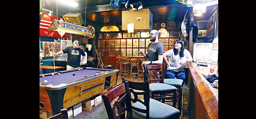 圖為佛州塔拉哈西的一家酒吧。疫情緩解後酒吧重開,三名常客相隔數月終於可以再度光顧聊天。美聯社