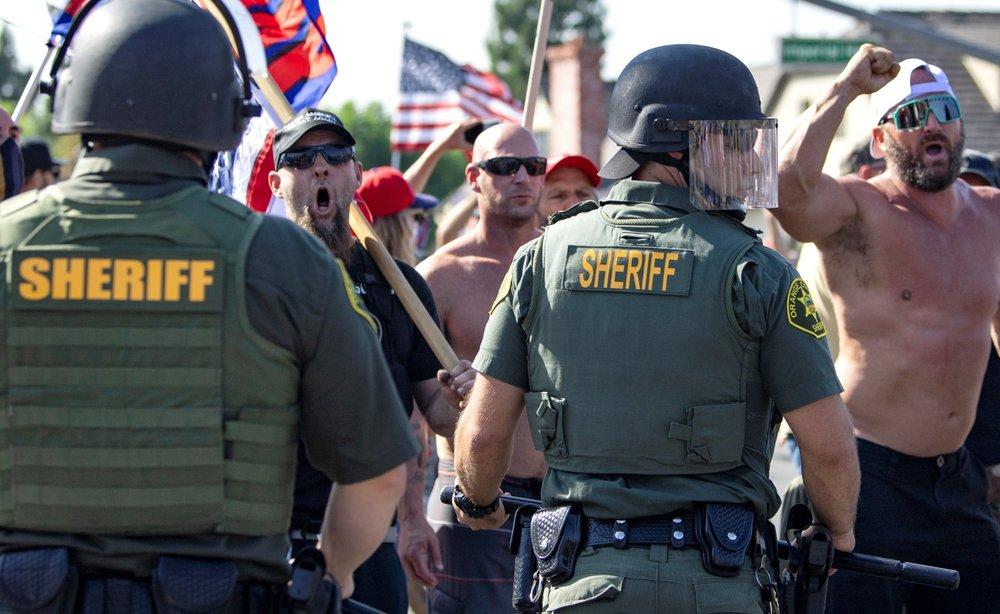 橙縣約巴林達市26日BLM抗議群眾和特朗普支持者的反抗議者群眾陣營對峙叫囂,警方部署大批警力將兩造隔開。美聯社
