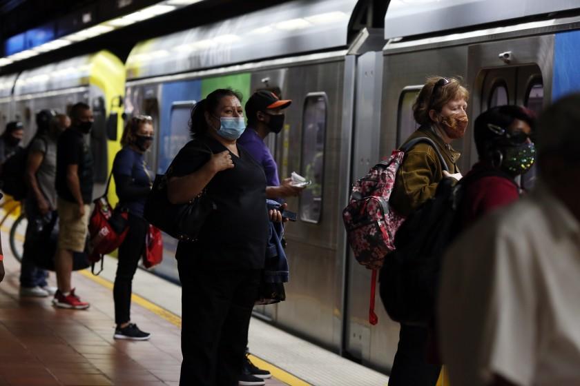 洛杉磯民眾戴口罩排隊等待搭乘地鐵。洛杉磯時報