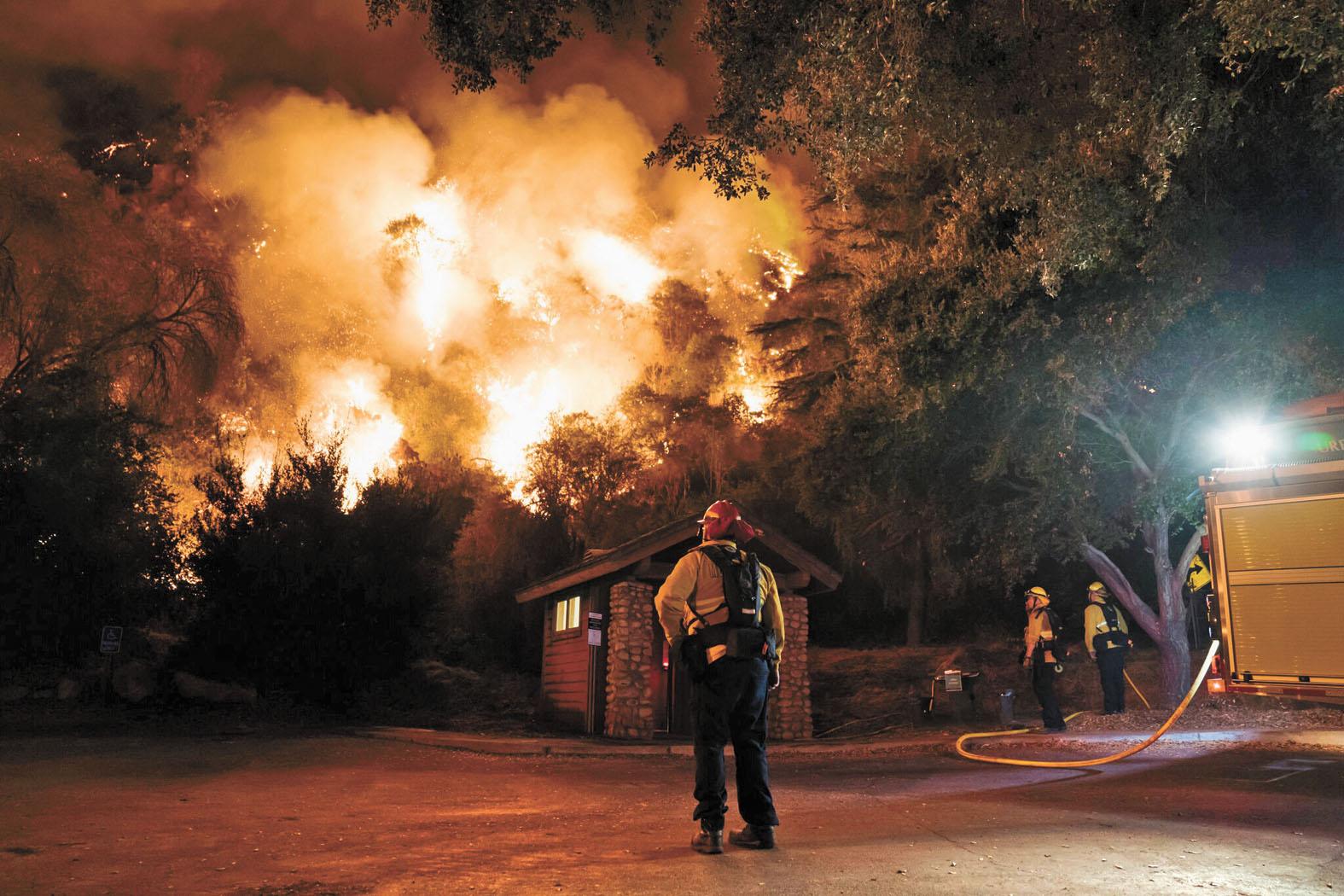 南加州消防員連夜先燒出一道阻隔用的防火牆,阻止加州蒙羅維亞的山貓大火的蔓延。紐約時報
