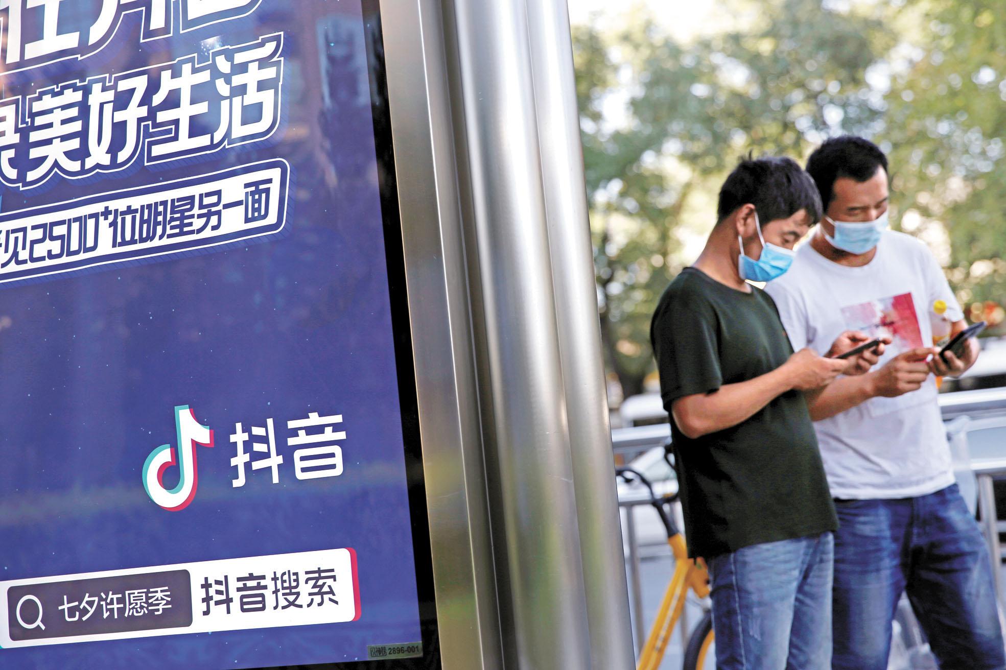 戴口罩的行人經過北京一個巴士站的TikTok廣告。路透社