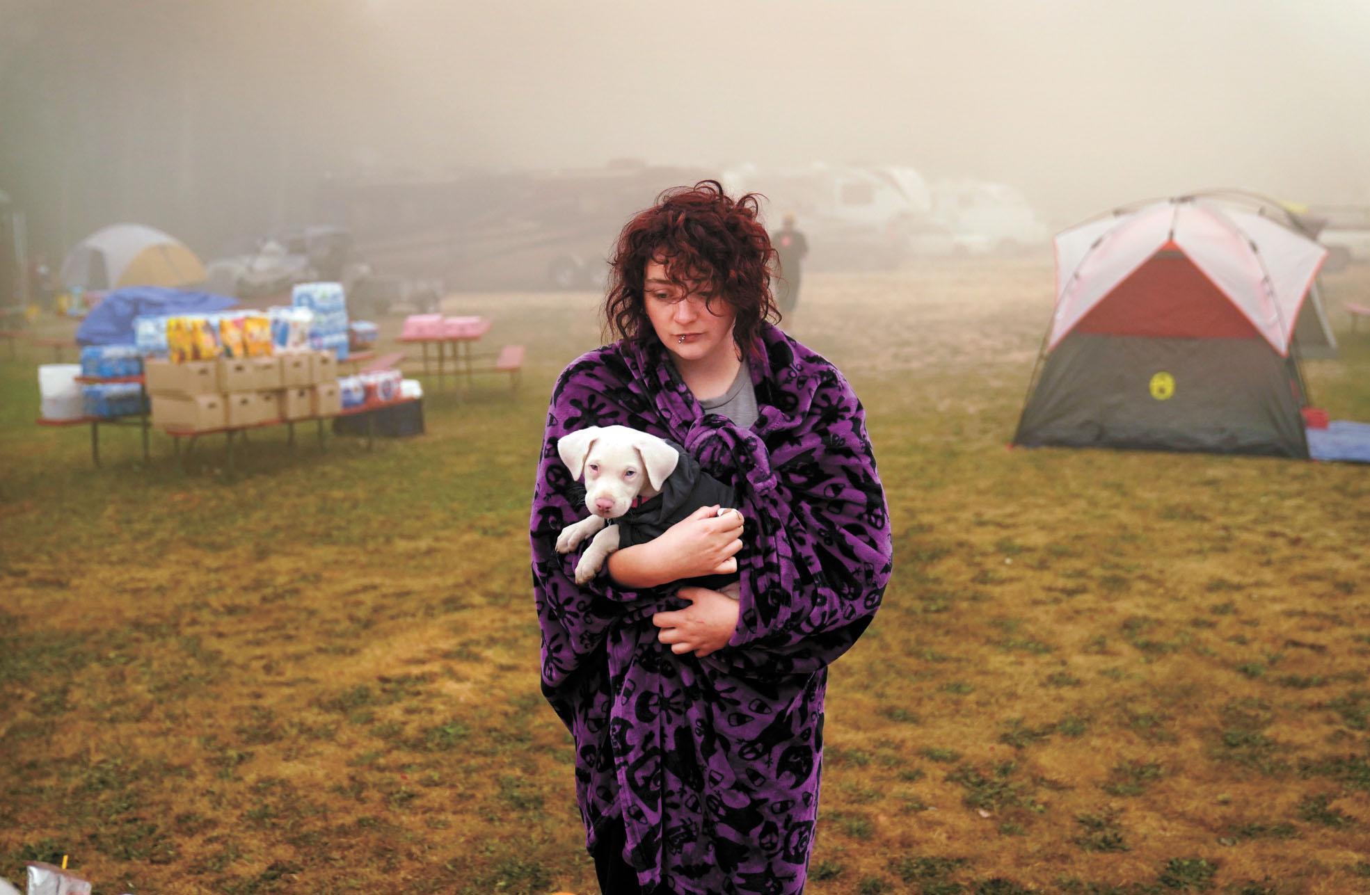 俄勒岡州橡木叢(Oak Grove)居民Shayanne Summers住在庇護中心已數天,懷抱寵物狗表情無奈。美聯社
