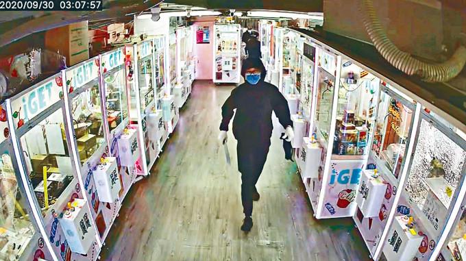 其中一匪持刀在店內協助同黨搶掠。
