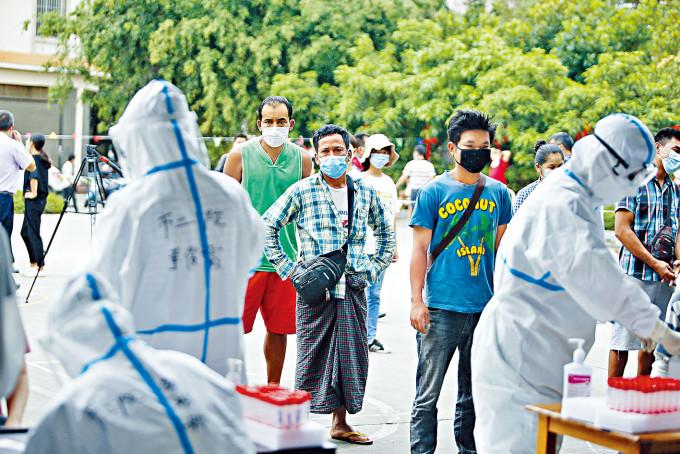 發現偷渡人員染疫的雲南瑞麗市,緬甸籍居民排隊檢測。