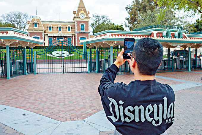 今年三月中加州迪士尼樂園受新冠疫情影響關門,一名男子在關門首天於閘門外拍照。