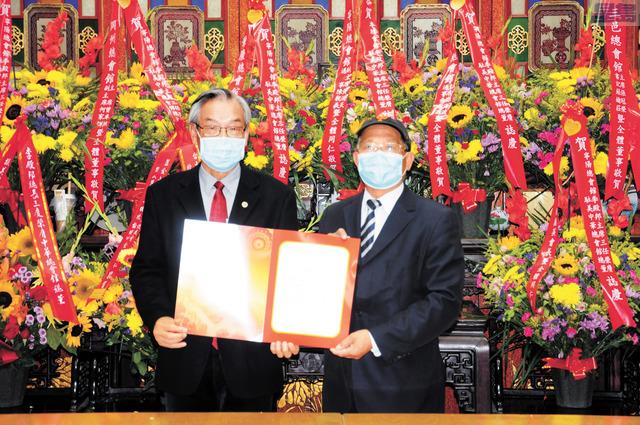 前任總董蔣澤綿(右)代表中領館總領事王東華向新任總董李殿邦(左)致送賀狀,以示祝賀。 馬紅兵攝