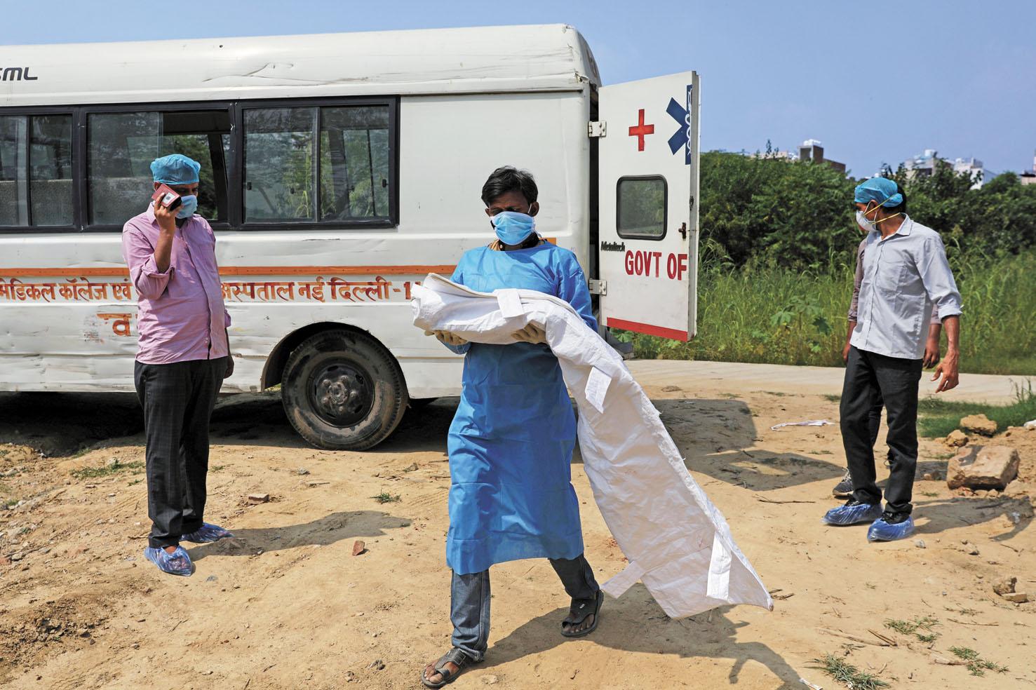全球死於新冠肺炎的人數破百萬人,圖為印度一名死於新冠肺炎的三個月大嬰兒葬禮上,男子抱著孩子的屍體。路透社