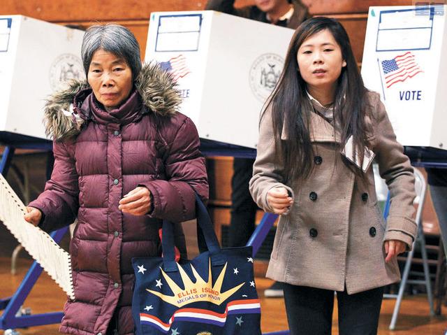 紐約一名翻譯人員(右)協助華裔耆老投票。美聯社檔案照