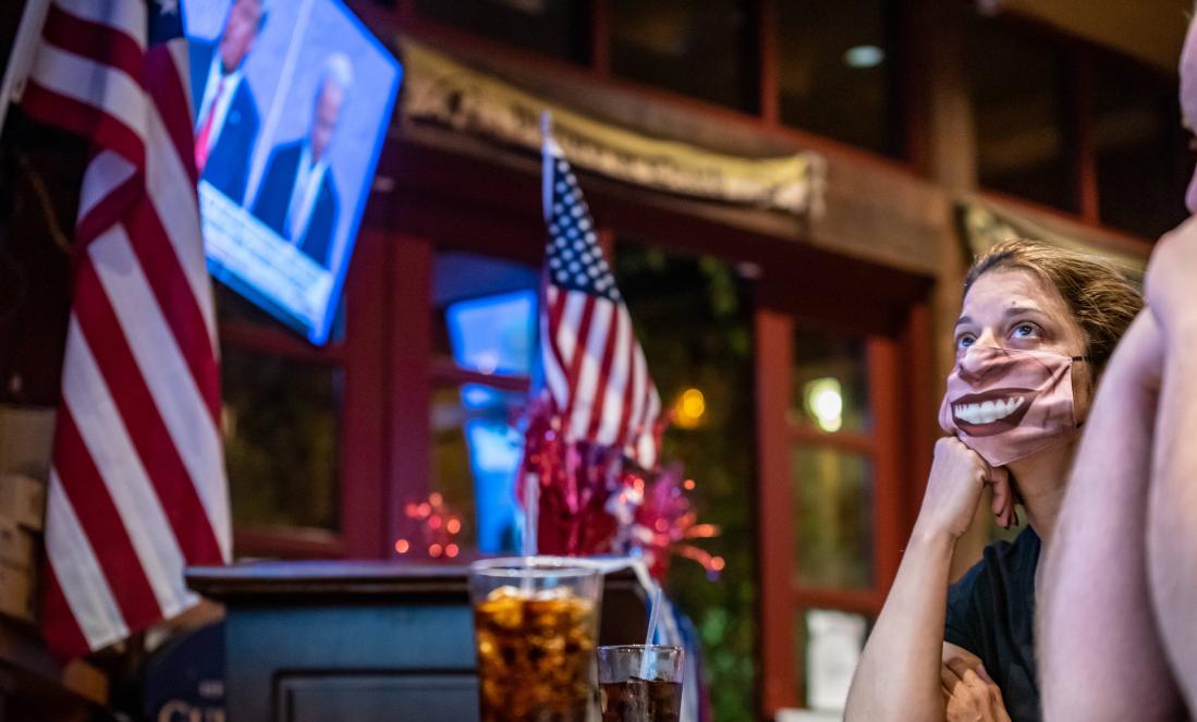 圖為德州聖安東尼奧市民馬丁內斯,戴口罩在酒吧觀看美國大選最後一場總統候選人電視辯論。    法新社