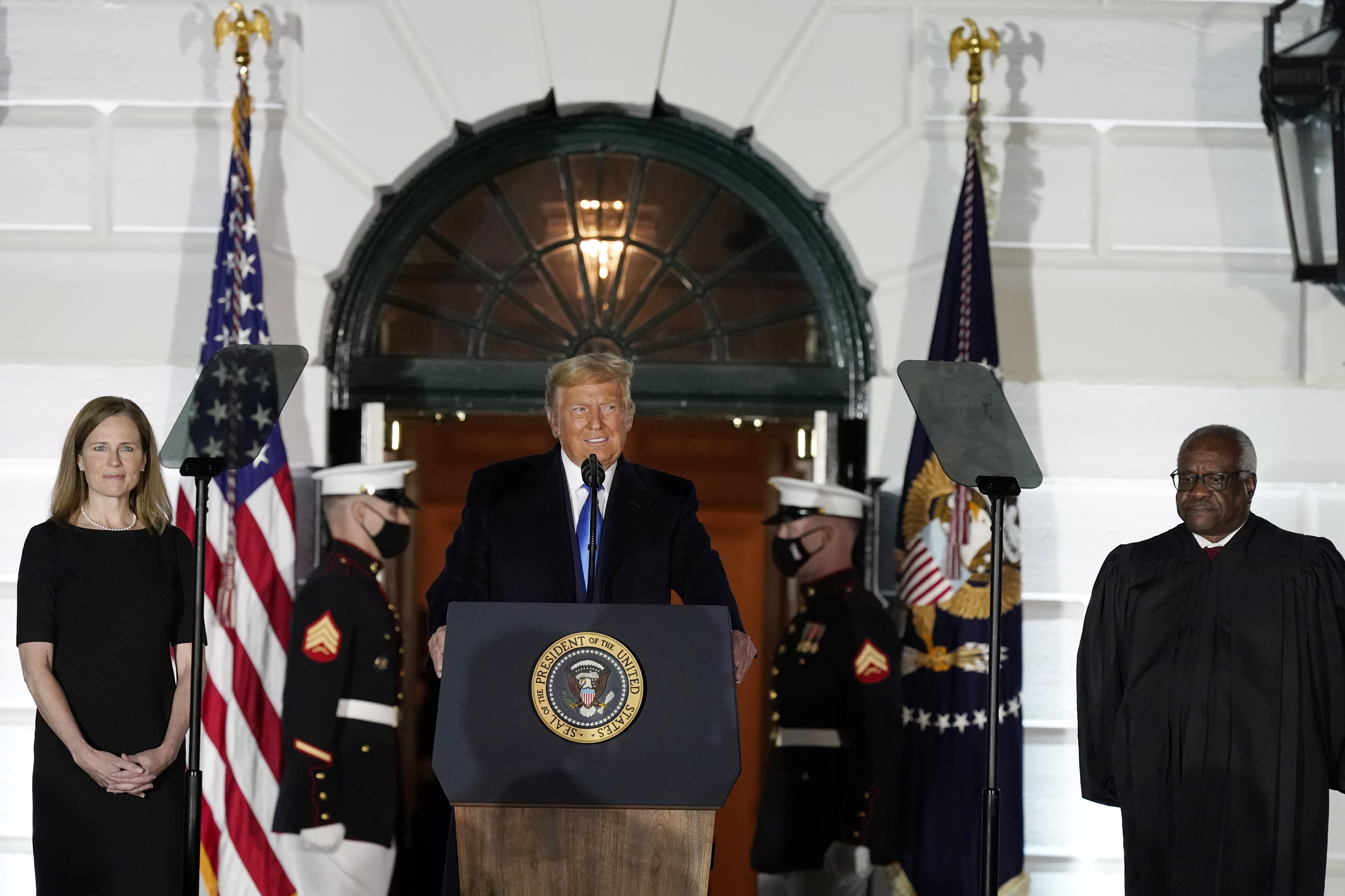 總統特朗普在巴瑞特(左)宣誓出任最高法院大法官之前,發表講話,右邊為另一最高法院大法官托馬斯,準備為巴瑞特監誓。    美聯社