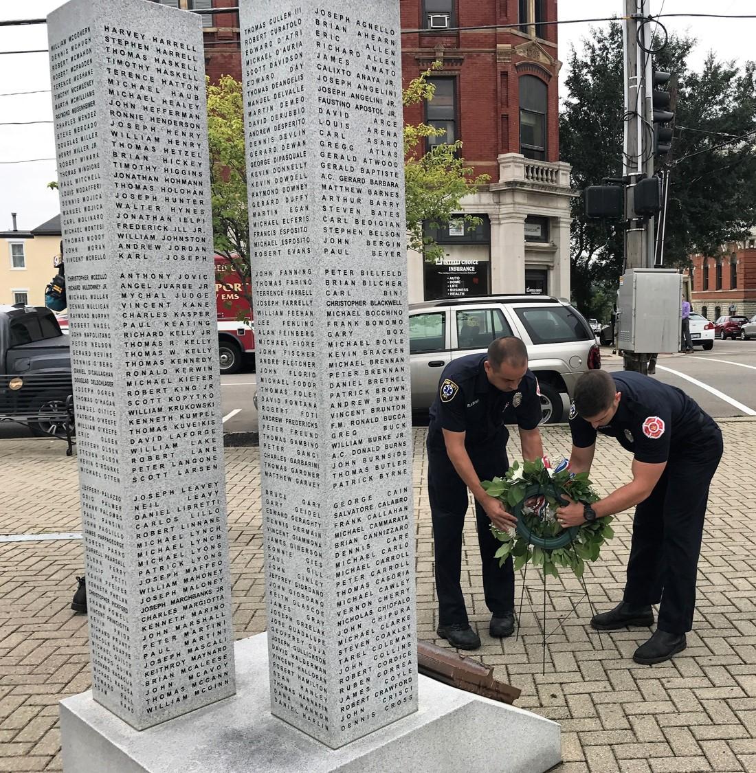 圖為紐約市消防消防員在紐波特紀念柱底部,放上一個悼念花圈。 NKyTribune圖片