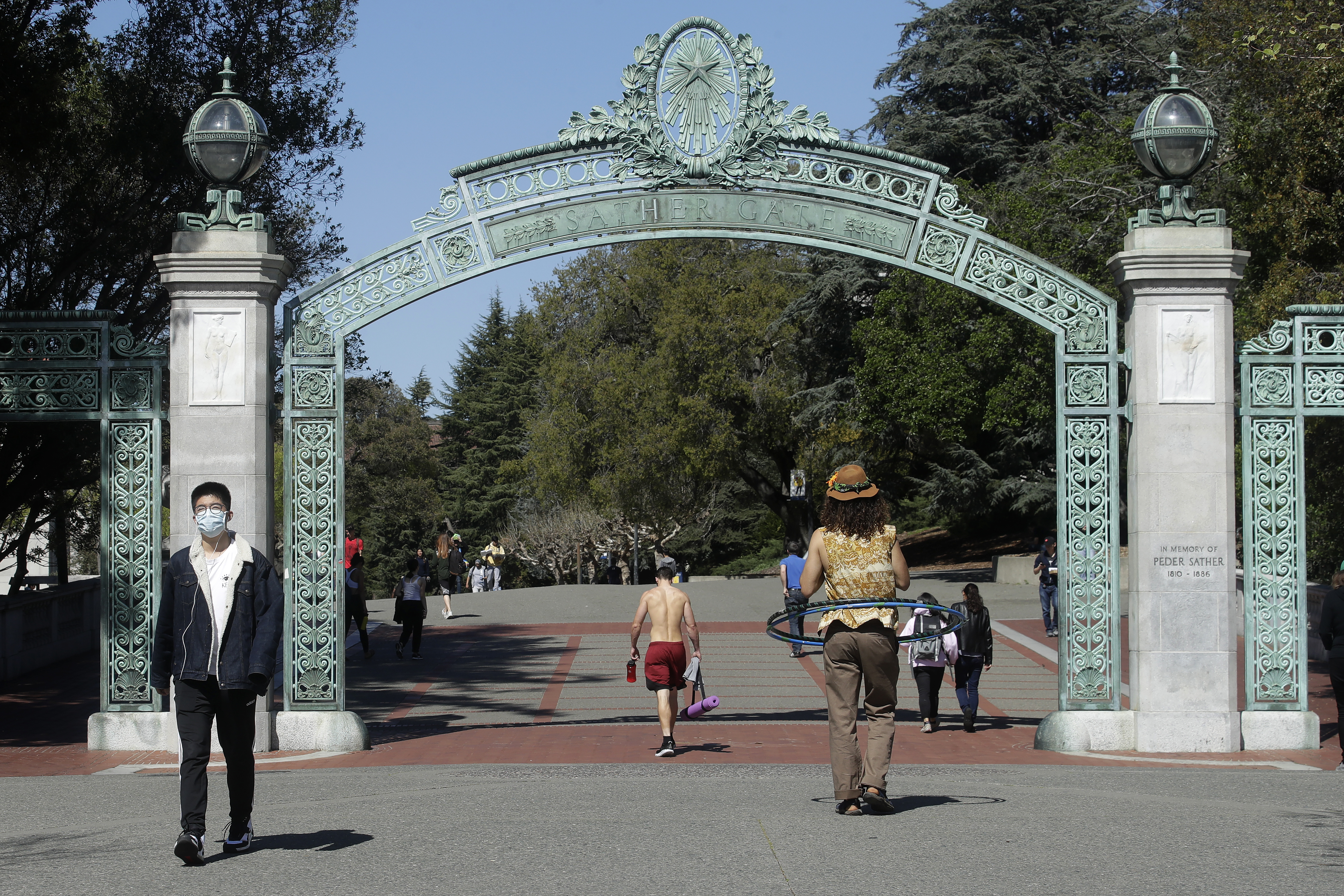 A man wears a mask while walking past Sather Gate on the University of California at Berkeley campus in Berkeley, Calif., Wednesday, March 11, 2020. (AP Photo/Jeff Chiu)