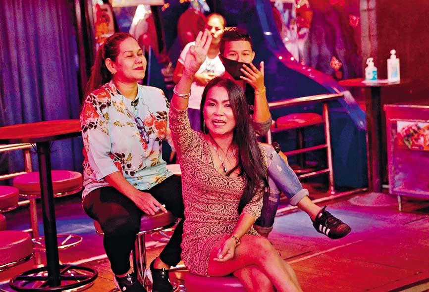 曼谷一名女子 在酒吧展示三指 手勢,支持示威 者。 路透社