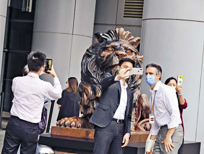 市民用不同拍照方 式,爭取攝下銅獅復修 後的容貌。 褚樂琪攝